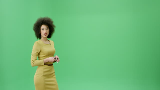 multi ethnic woman with curly black hair presenting the weather forecast - green background stock videos & royalty-free footage