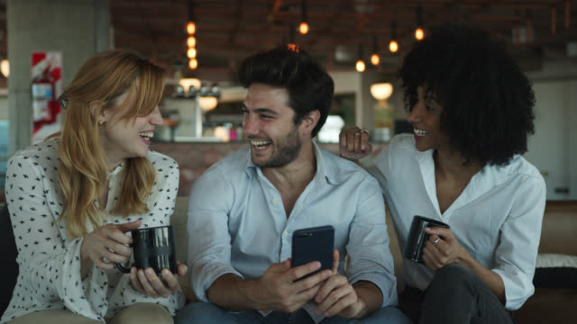 multi ethnic young business people at a coworking office taking a break enjoying coffee and looking at something funny on smartphone - coffee variation stock videos & royalty-free footage