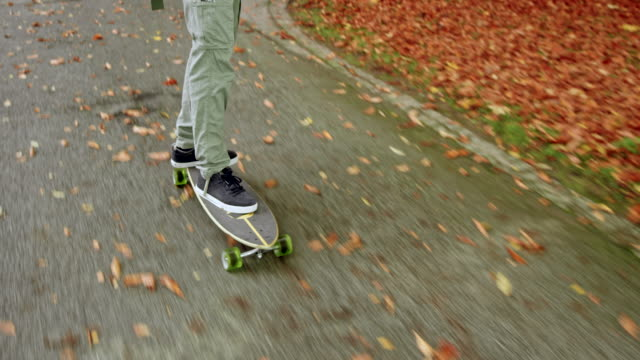 multi ethnic young man listening to music while riding his longboard in a park - grey jacket stock videos and b-roll footage