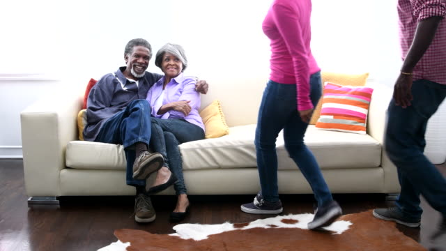 Multi generation African American family walking to sit on sofa