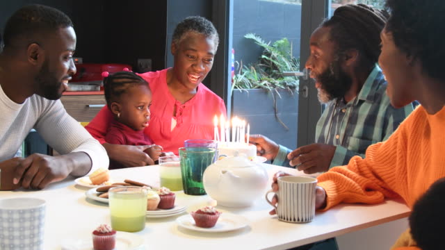 Multi generation African family singing happy birthday with birthday cake