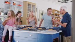 Multi Generation Family Around Kitchen Island Eating Takeaway Pizza Together
