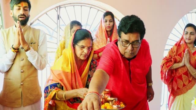vídeos y material grabado en eventos de stock de familia de múltiples generaciones asistiendo a una oración hindú tradicional en un templo - servicio religioso