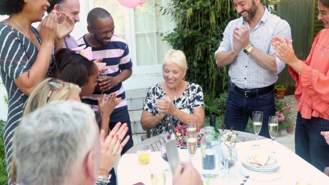 multi generation family clapping grandmother blowing out birthday cake candles at patio table - 40 49 years stock videos & royalty-free footage