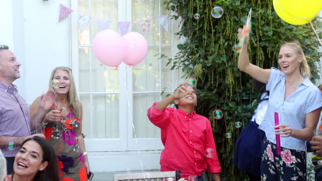 multi generation family enjoying birthday party blowing bubbles on patio - bubble wand stock videos & royalty-free footage
