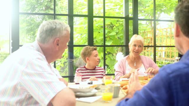 multi generation family having breakfast at dining table - 食事点の映像素材/bロール