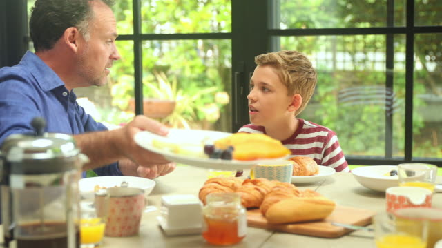 multi generation family having breakfast at dining table - 団らん点の映像素材/bロール