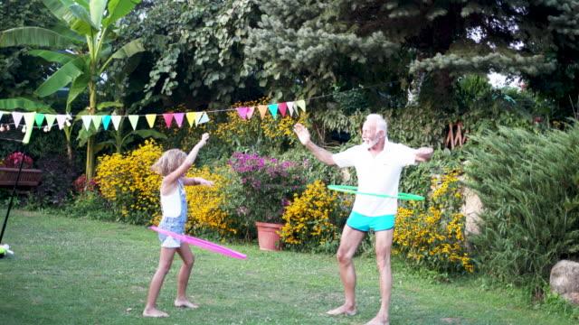 stockvideo's en b-roll-footage met multi generatie familie hula hooping in achtertuin - jong van hart