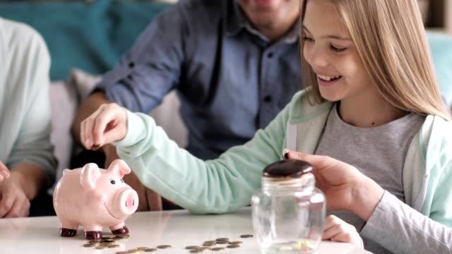 vidéos et rushes de argent de famille d'épargne de multi génération - tirelire