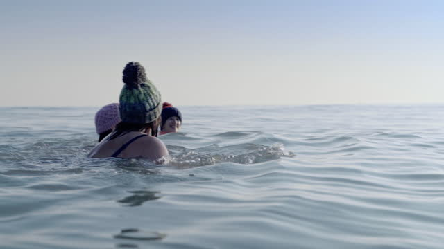 multi generation family swimming in the sea in winter from left to right - cold temperature stock videos & royalty-free footage