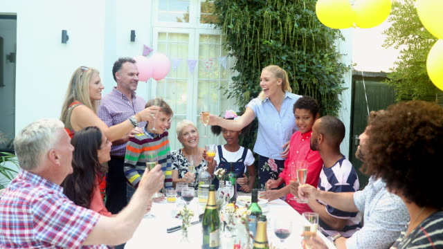Multi generation family toasting champagne glasses at birthday party on patio