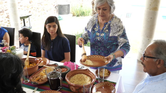 multi generation mexican family having lunch - etnia latino americana video stock e b–roll