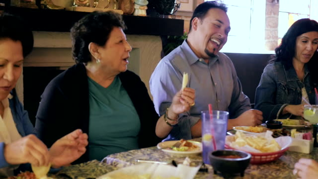 multi generational hispanic family enjoying meal together in mexican restaurant - 拉丁美洲人和西班牙裔人 個影片檔及 b 捲影像