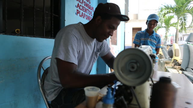 santo domingo dominican republic november 30 2012 multiclip of a young man who is operating a sewing machine at the market in santo domingo in the... - サントドミンゴ点の映像素材/bロール