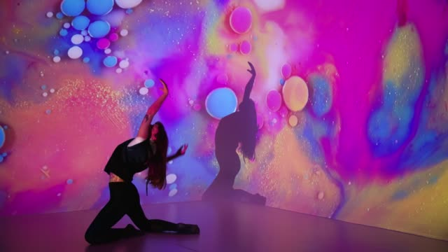 Multicolor background projection upon a female dancer