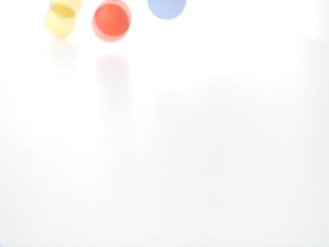Multicolored Balls Bouncing Across Table
