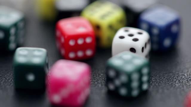 vídeos de stock, filmes e b-roll de cu selective focus multicolored dice spinning - jogo da sorte