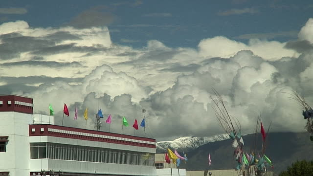 ms multicolored flags on building and large clouds in sky, lhasa, tibet - medium group of objects stock videos & royalty-free footage