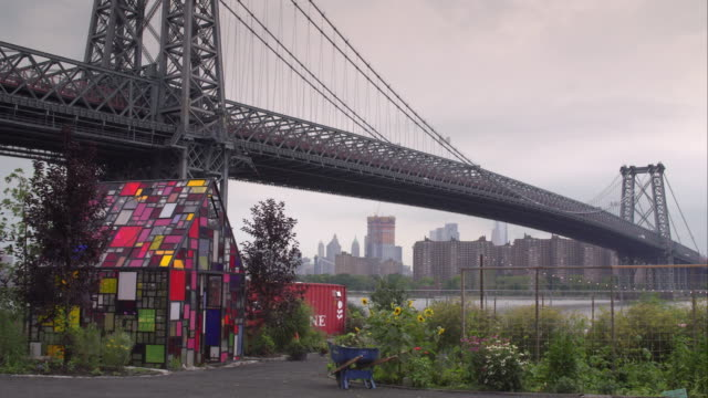 vídeos de stock, filmes e b-roll de multicolored greenhouse sits beneath the williamsburg bridge in a community garden along the east river. - williamsburg new york