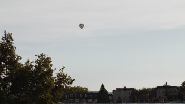 vídeos de stock, filmes e b-roll de multicolored hot air balloon crossing the skyline (wide) - festa do balão de ar quente