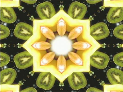 cgi multi-colored kaleidoscope pattern with kiwis, strawberries, grapes + apples - digital animation bildbanksvideor och videomaterial från bakom kulisserna