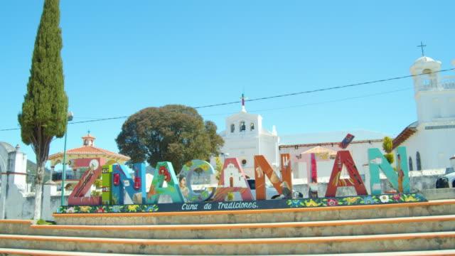vídeos de stock e filmes b-roll de multi-colored landmark banner in front of a church in zinacantan, chiapas. pueblo mágico in mexico - chiapas