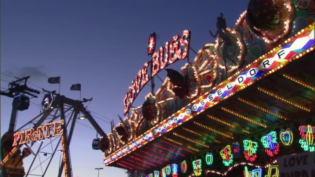 CU ZO MS Multicolored neon signs on Love bugs ride in amusement park at dusk, Dallas, Texas, USA