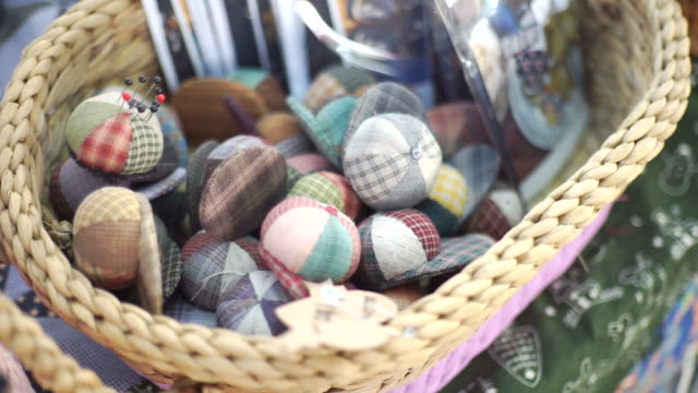 multicolored patchwork needle pillows in a wicker basket, handmade and handicraft concept. - patchwork stock videos & royalty-free footage
