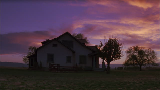a multi-colored sky silhouettes trees and a small farmhouse. - ranch stock videos & royalty-free footage