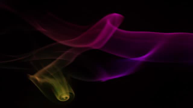 vidéos et rushes de fumée multicolore clignotant sur le fond noir - touche de couleur