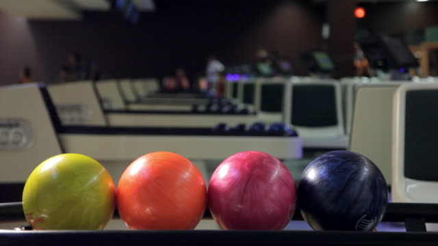 multicoloured bowling balls in return system - ボウリング点の映像素材/bロール