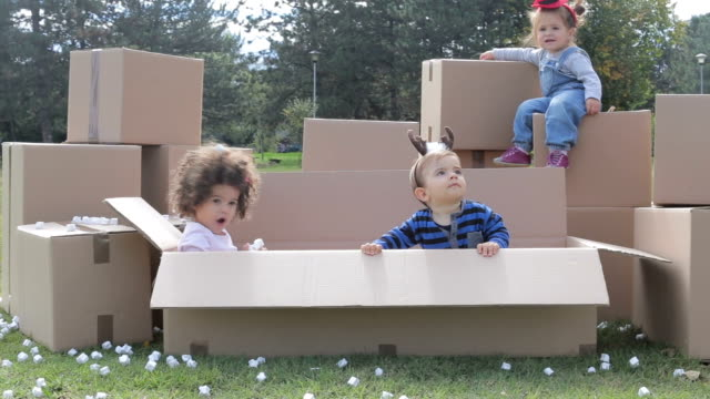 multicultural babies playing in cardboard boxes , throwing styrofoam peanuts and having fun - polystyrene stock videos & royalty-free footage