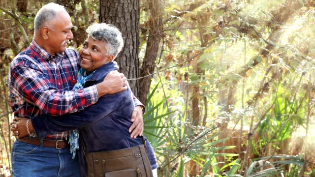 multi-ethnic, active senior adult couple hiking in wooded forest area. - young at heart stock videos & royalty-free footage