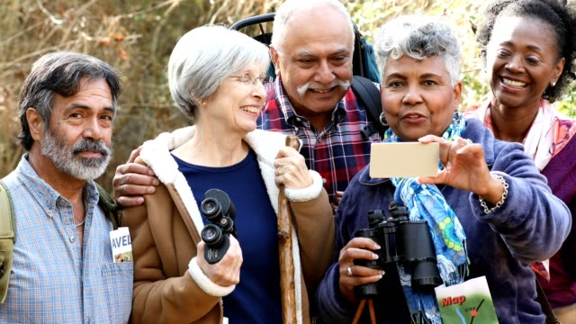 multi-ethnic, active senior adult friends hiking in wooded forest area. - osservare gli uccelli video stock e b–roll