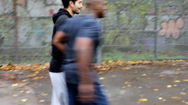 vidéos et rushes de multiethniques athlètes jouant au soccer durant l'automne - plaque rue