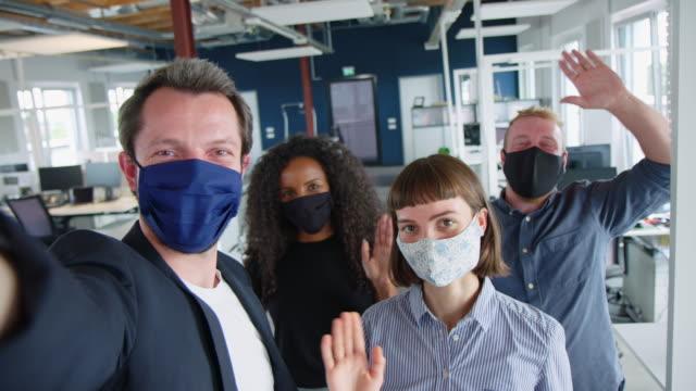 vídeos de stock, filmes e b-roll de colegas de negócios multiétnicos com máscaras faciais tirando selfie - fotografia arte e artesanato