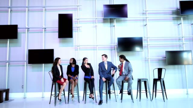 vidéos et rushes de gens d'affaires multiethnique assis dans la rangée de parler - débat