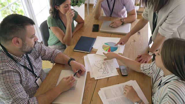 vidéos et rushes de équipe d'affaires multiethnique ayant une réunion et discutant de la stratégie d'affaires à la table de conférence dans un milieu de travail moderne - étude de marché