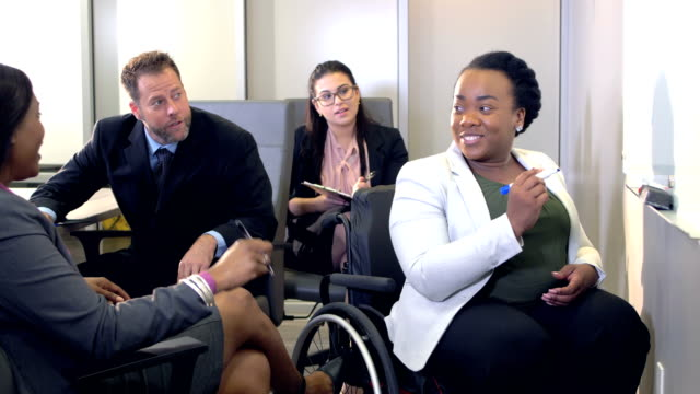vídeos de stock e filmes b-roll de multi-ethnic business team meeting, woman in wheelchair - employee engagement