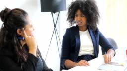 Multi-ethnic businesswomen are discussing at desk