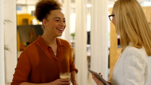 Multi-ethnic businesswomen communicating in creative office