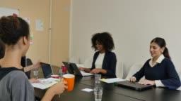 Multi-ethnic businesswomen leaving from board room