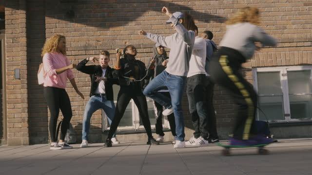 vídeos de stock, filmes e b-roll de multi-ethnic cheerful friends dancing on street in city - hobbie