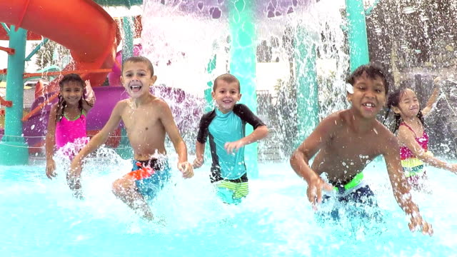multi-ethnic children at water park playing, splashing - children only stock videos and b-roll footage