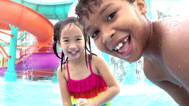 Multi-ethnic children at water park playing, splashing
