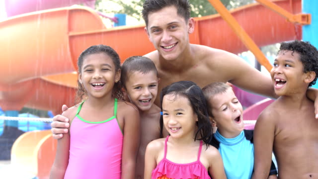 multi-ethnic children, counselor at water park by slide - summer camp helper stock videos & royalty-free footage