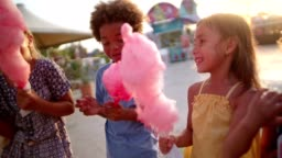 Multi-ethnic children eating cotton candy and pop-corn at amusement park
