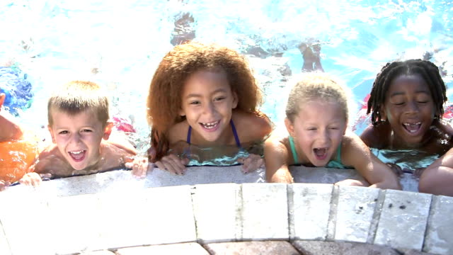 Multi-ethnic children hanging on side of swimming pool
