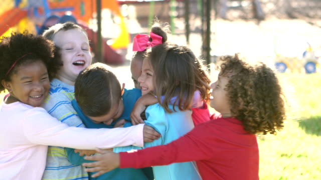 vídeos de stock e filmes b-roll de multi-ethnic children hugging on playground - criancas
