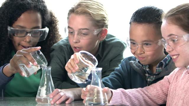 Multi-ethnic children in chemistry lab